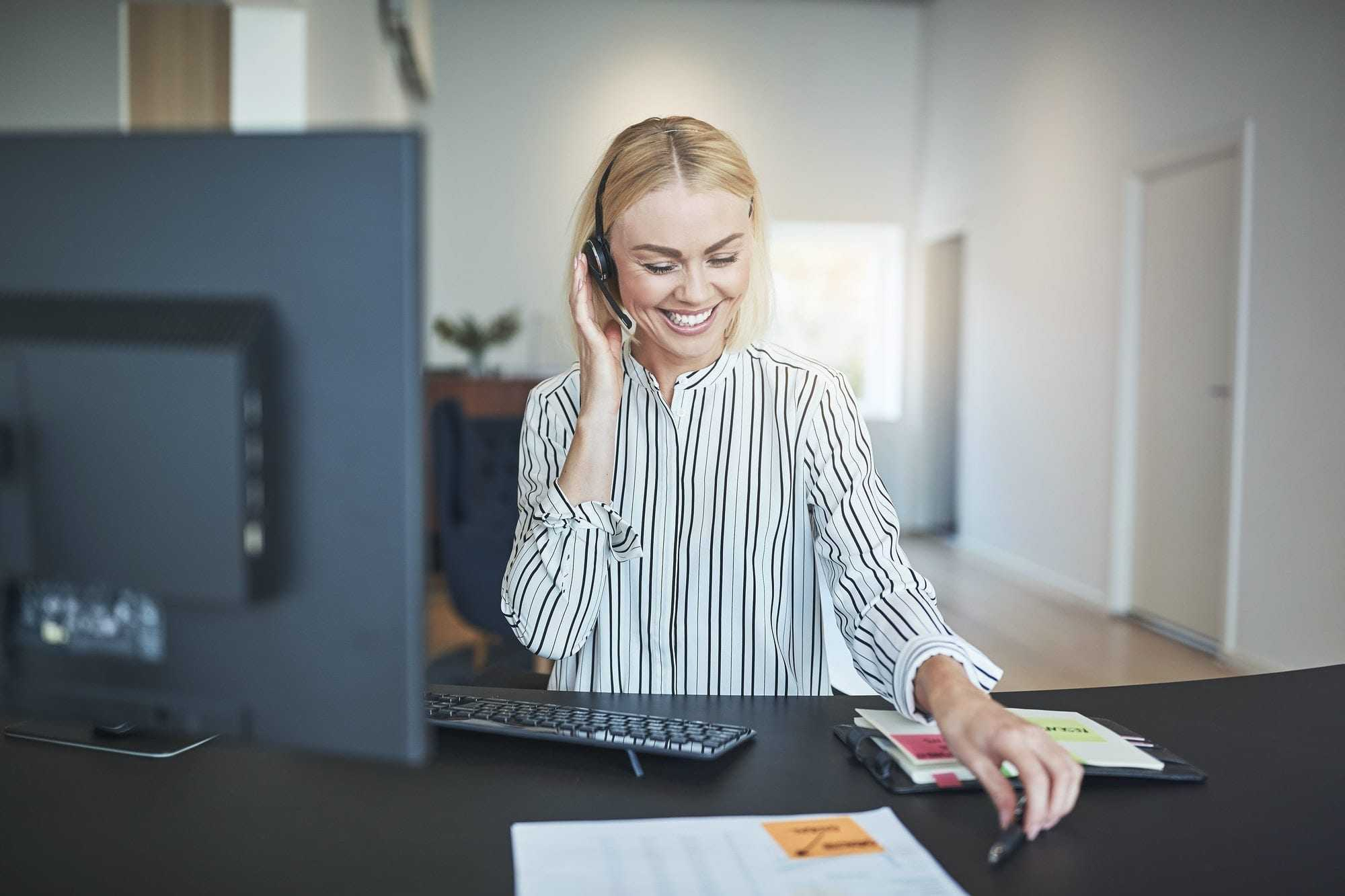 Laughing businesswoman talking on a headset at her office desk