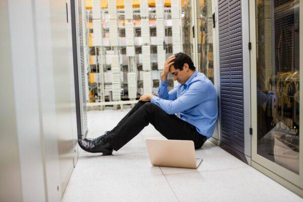 Stressed technician sitting in hallway